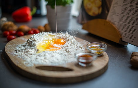 selective focus photography of raw egg surrounded by flour