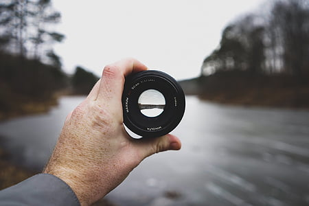 selective focus photography ofhuman hand hand holding black zoom lens