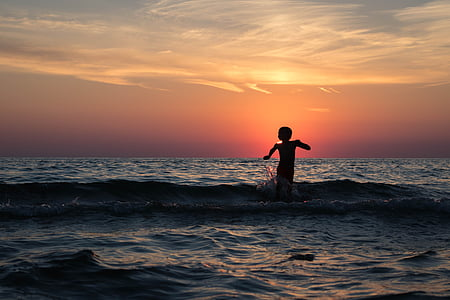 child on body of water under yellow and orange sunset