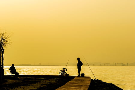 silhouette o man standing in front of body of water