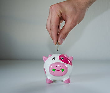 person putting coin on white, pink, and red piggy bank