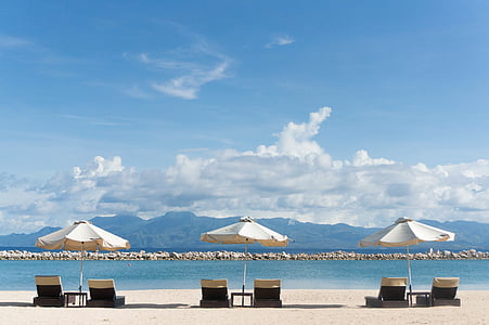 three white patio umbrella on black coffee tables with six fainting lounges near seashore