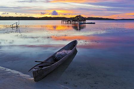 canoe docked on seashore during golden hour