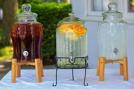 three clear beverage dispensers on top of table