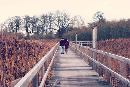 couple walking on the wooden dock