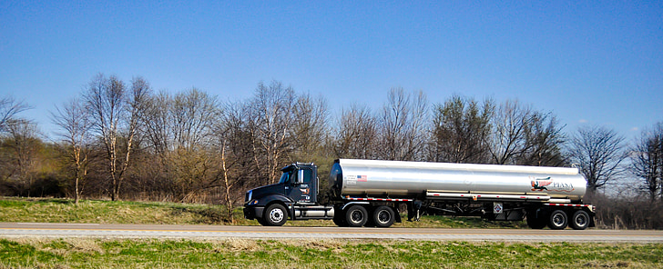 gray and black tanker truck traveling on road at daytime