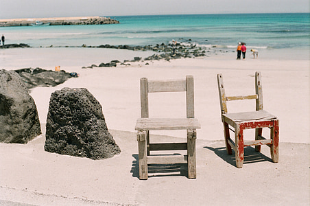 photo of two black wooden chairs near seashore