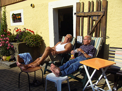 two men sitting on lounge outdoor