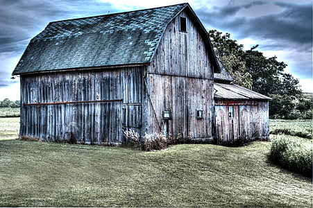 gray wooden shed under cloudy sky