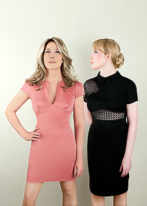 woman looking on other woman wearing pink dress