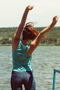 woman raising hands facing body of water