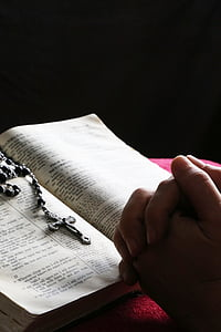 person praying in front of the rosary and bible