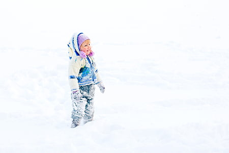 toddler girl standing on snow covered ground
