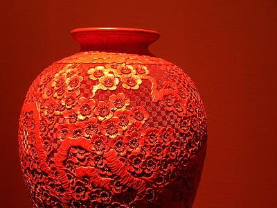 focus photo of red floral ceramic vase