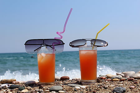 two black sunglasses on top on clear drinking glasses filled with orange liquid on the beach during daytime