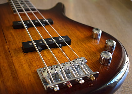 shallow focus photography of brown 4-stringed electric bass guitar