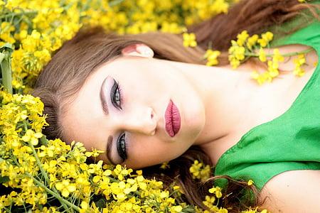 woman in green shirt lying on yellow flower field