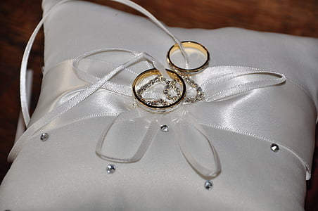 two gold-colored rings on top of white throw pillow