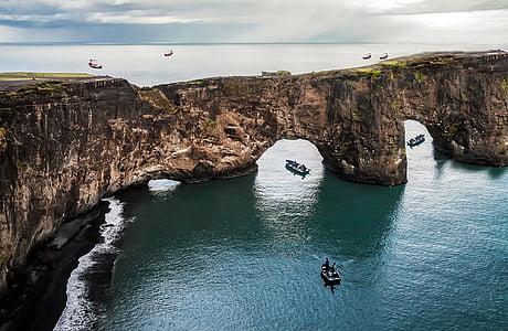 boats near rock formation