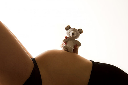 woman holding grey teddy bear on top of her belly