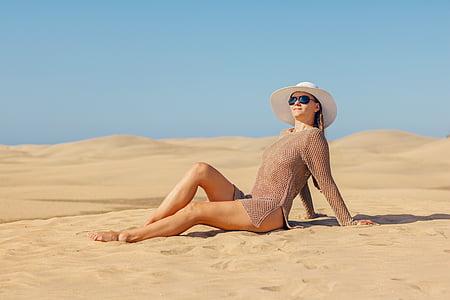 photo of woman sitting on seashore during daytime
