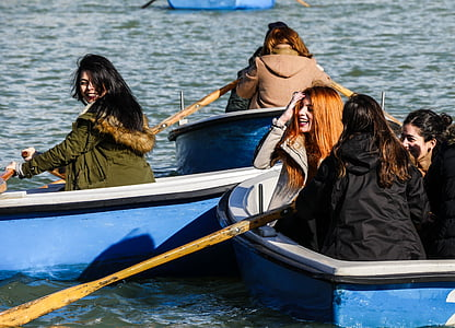 women riding on boat rowing towards each other
