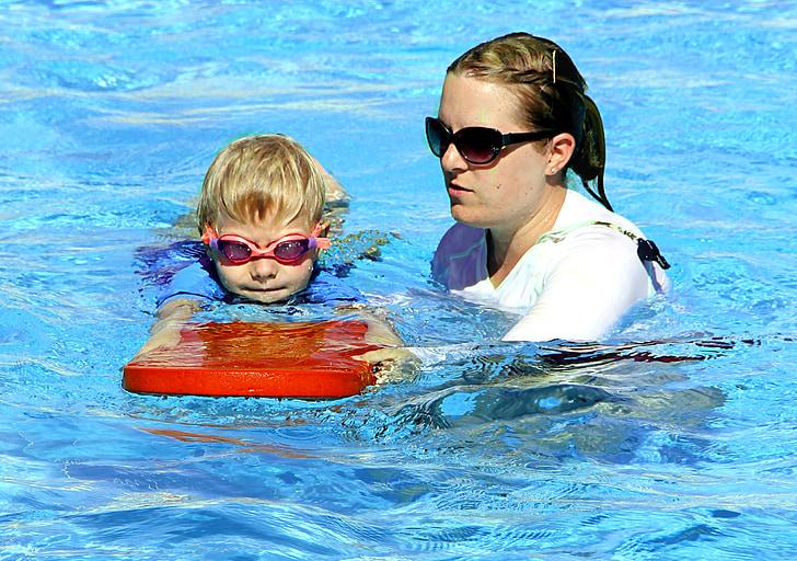 woman teaching boy to swim