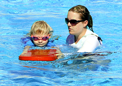 woman teaching boy to swim