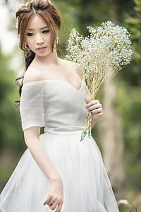 woman wearing white off-shoulder wedding dress holding white petal flower