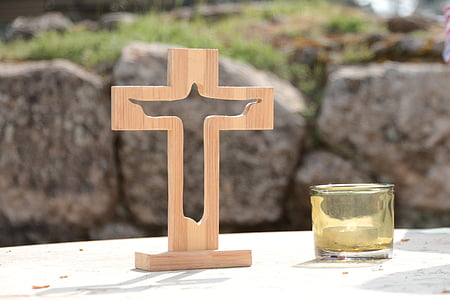 beige wooden cross beside glass candle holder
