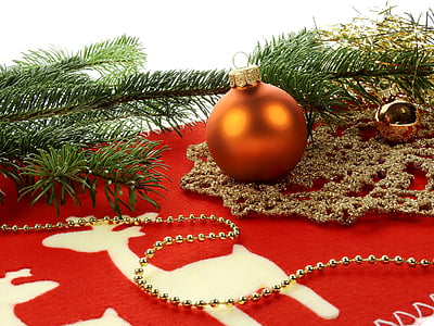 orange Christmas bauballs on red cloth