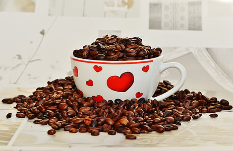 coffee beans on white and red ceramic mug