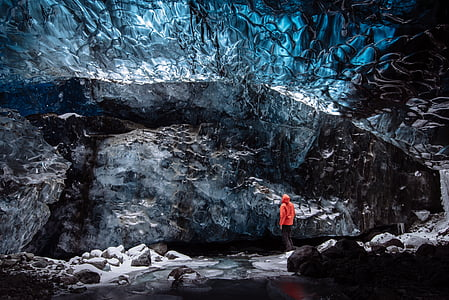 person standing in front of cave