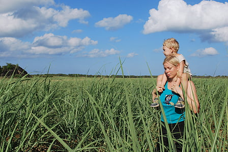 mother carrying her child while standing on grass field