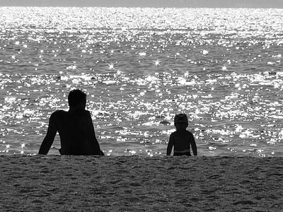 silhouette of man and child facing seashore during daytime