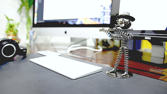 Apple magic keyboard near stainless steel spring human playing flute figurine