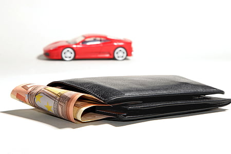 black leather bi-fold wallet with banknotes beside red die-cast toy