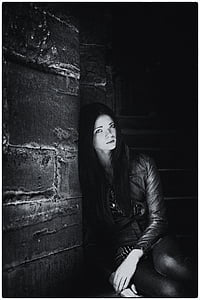 grayscale photo of woman leaning on gray wall