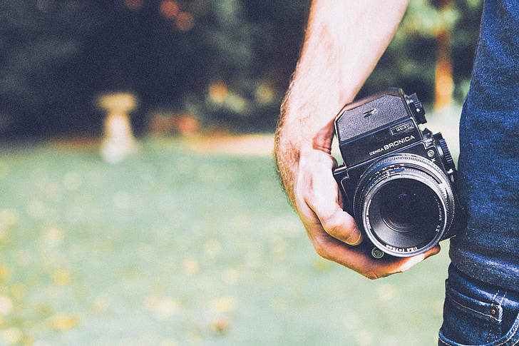 selective focus photography of man holding DSLR camera