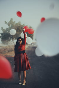 selective focus of woman in red dress holding balloon