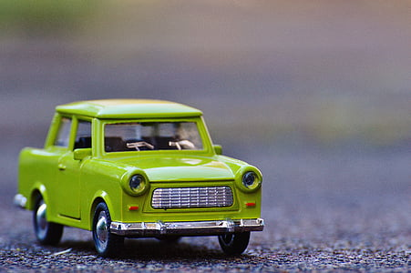 selective focus photography of green car die-cast metal model on concrete road at daytime
