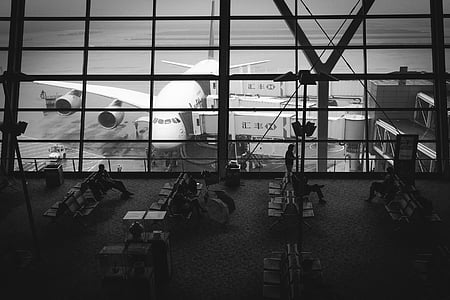 grayscale photo of people sitting on airport waiting bench