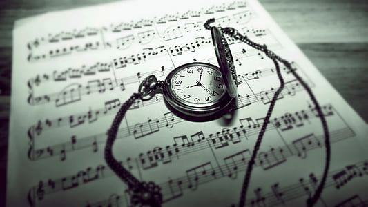 round silver-colored pocket watch on white music note paper