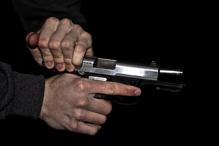 person holding gray semi-automatic pistol