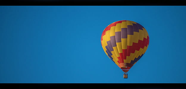 yellow, purple, and red floating hot air balloon