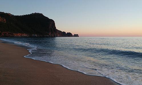 seashore and mountain during sunrise