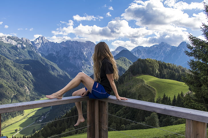 woman in black shirt in front of mountains