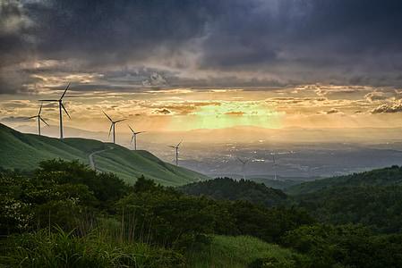 green trees near windmill under cloudy sky