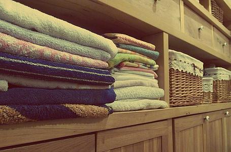 assorted-color towels on wooden shelf