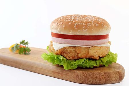 chicken ham burger on brown wooden chopping board